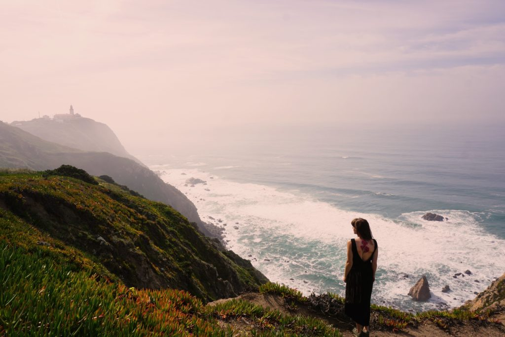 Denisa standing at the coast of Portugal looking to the distance at the lighthouse