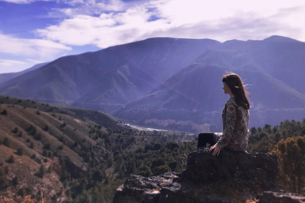 Sitting on a rock looking into distance to find meaning of life and thoughts on the life in a community